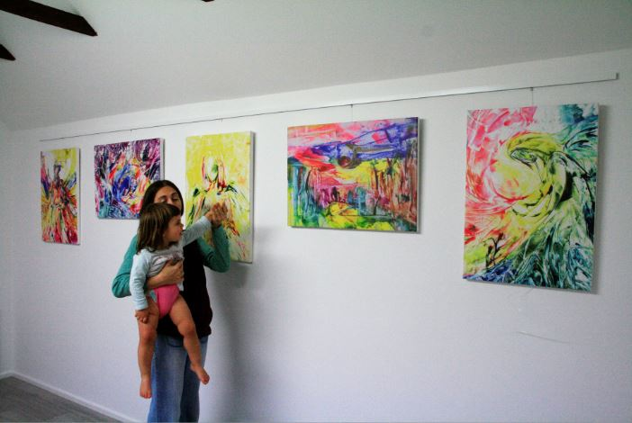 Woman and child lookign at paintings. Encaustic Art painting Exhibition, England, UK. Nov 2018.