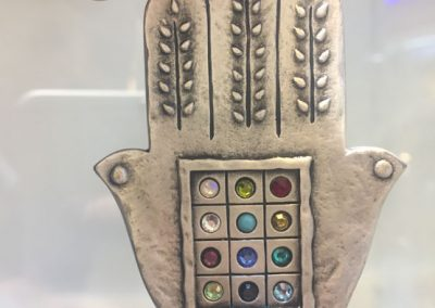 The symbolic 'HamSa', a palm-shaped amulet. This one contains 12 stones, representing the 12 tribes of Israel. (Photo: Gil Dekel, 2019).